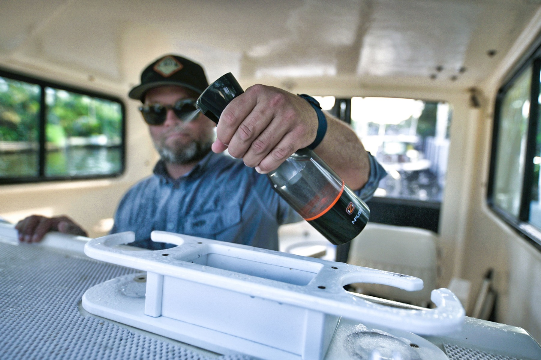 man cleaning boat with oz nfuse ozone sprayer